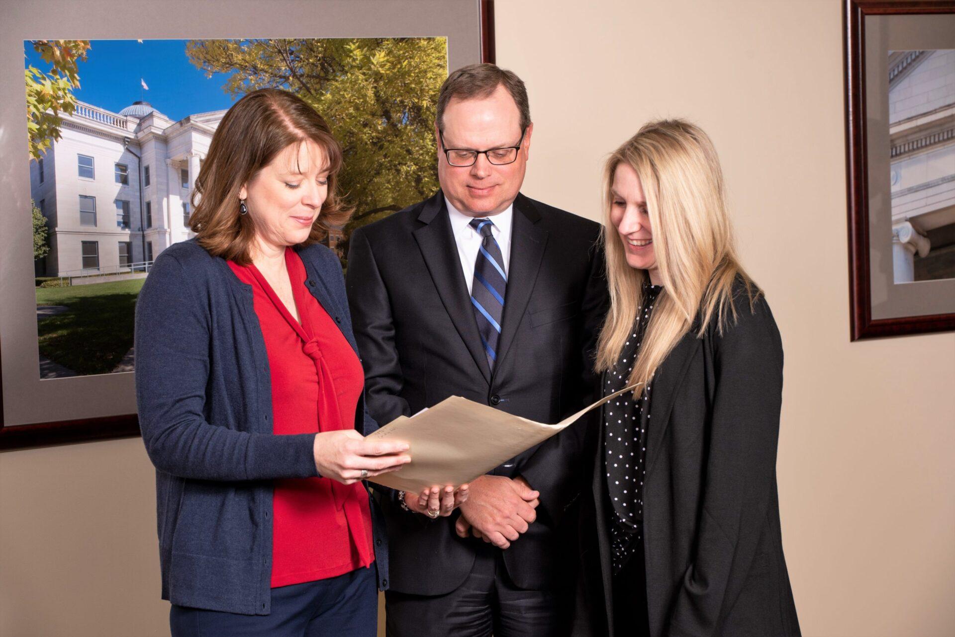 Casey Elliot, Karen Hajicek, and Thomas Harrison looking over legal documents